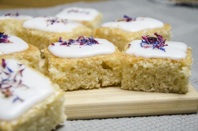 Veganer Zitronenkuchen mit Zuckerguss und essbaren Blüten